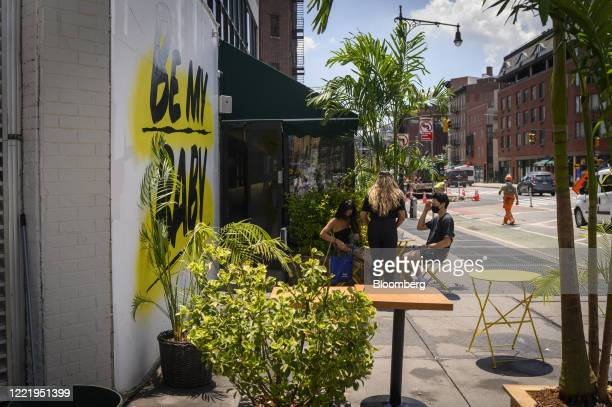 Server assists customers outside of the Baby Brasa restaurant in the West Village neighborhood of New York, U.S., on Monday, June 22, 2020. No city...