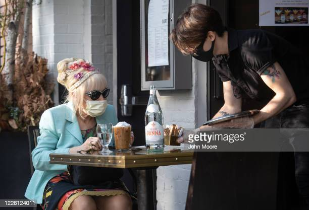 A server brings out sweetener to patron Francesca Macartney Beale at Douro restaurant on May 20 2020 in Greenwich Connecticut After two months of...