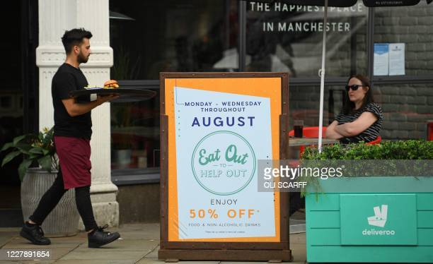"Server carries food past a sign promoting the British Government's ""Eat out to Help out"" COVID-19 scheme to get consumers spending again, outside a..."