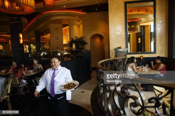 A server carries food to diners at a Cheesecake Factory Inc restaurant in the Canoga Park neighborhood of Los Angeles California US on Tuesday Aug 1...