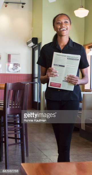 Server carrying menus in restaurant