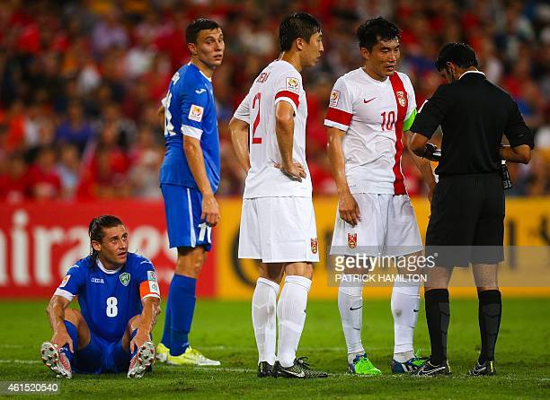 Server Djeparov and Jamshid Iskanderov of Uzbekistan and Ren Hang and Zheng Zhi of China look on as the referee gives a yellow card during the first...