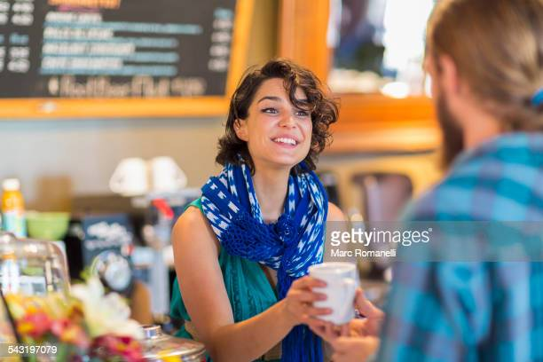 Server giving cup of coffee to customer in cafe