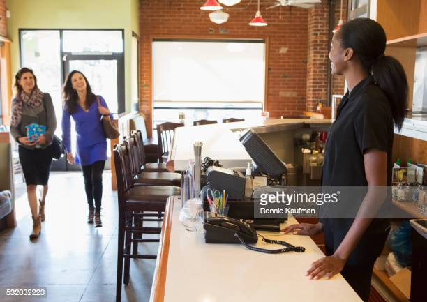 Server greeting customers in restaurant
