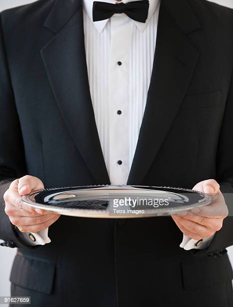 A server holding a silver tray