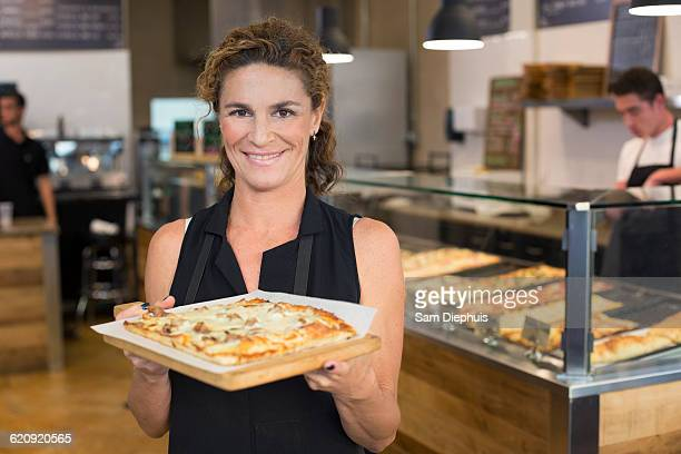 Server holding pizza in cafe