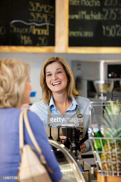 Server in supermarket talking with customer