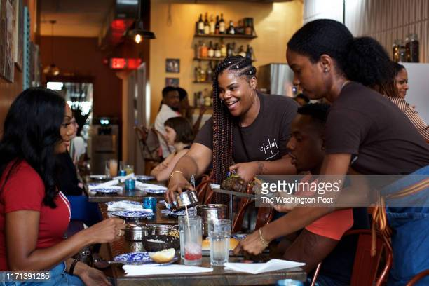 Server Jade Savoy serves a Paratha Tiffin Box to customers Akila Roberts and Keron Crooks at Cane photographed in Washington DC on May 30 2019