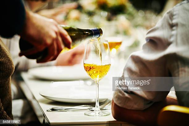 Server pouring glass of wine during dinner