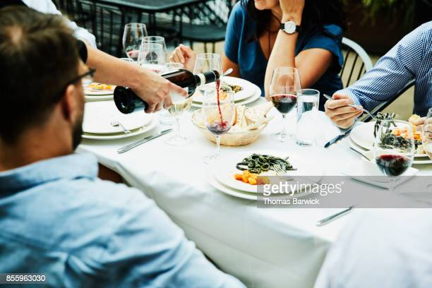 Server pouring wine for friends sharing celebration meal on restaurant patio