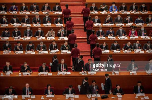 Server pours tea for Chinese President Xi Jinping, center, and lawmakers are served tea by hosts and hostesses at the opening session of the National...
