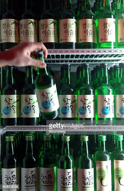 A server takes a bottle of soju out of the refrigerator at a bar in Seoul South Korea on Monday Dec 1 2008 A worldwide financial crisis and a...