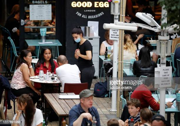 Server wearing a face mask or covering due to the COVID-19 pandemic, takes a customer's order as diners sit at tables outside a restaurant in London...