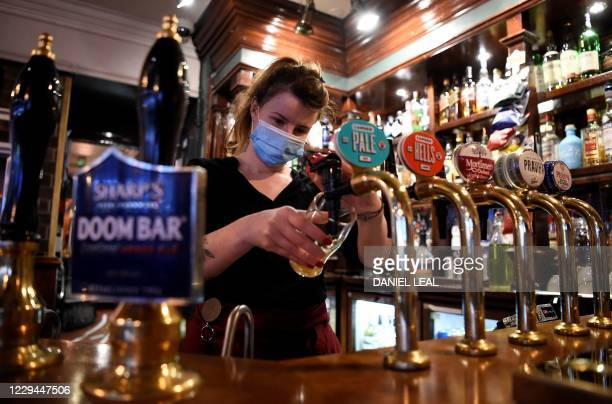 Server wearing a face mask or covering due to the COVID-19 pandemic, pours a pint of Camden Pale Ale inside a pub in Mayfair, London on November 3 as...
