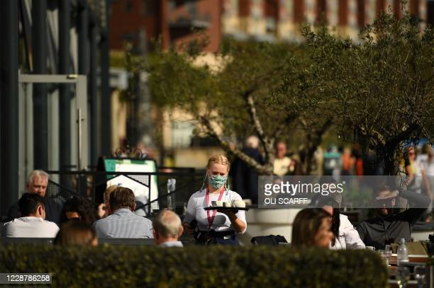 Server wearing a face mask or covering due to the COVID-19 pandemic, carries drinks to customers at the outside tables of a restaurant in Newcastle,...