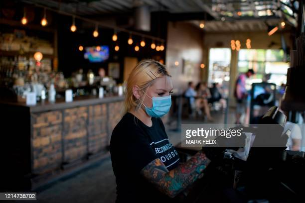 A server wearing a facemask and gloves rings up an order at Eight Row Flint in Houston Texas on May 22 amid the novel coronavirus pandemic