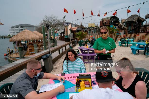 A server wearing a facemask takes an order from a table as Fish Tails bar and grill opens for in person dining amid the coronavirus pandemic on May...