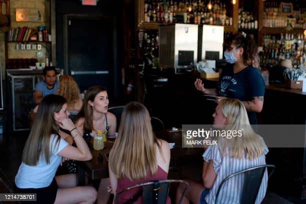 A server wearing a facemask takes orders from a table of customers at Eight Row Flint in Houston Texas on May 22 amid the novel coronavirus pandemic