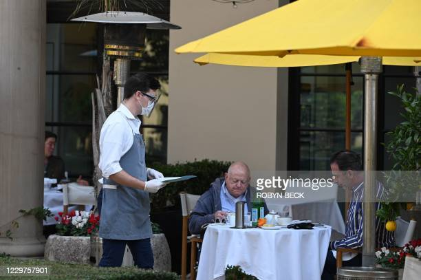 Server wearing a mask and face shield takes orders from customers at a restaurant in Beverly Hills, California, November 23, 2020. - Los Angeles...