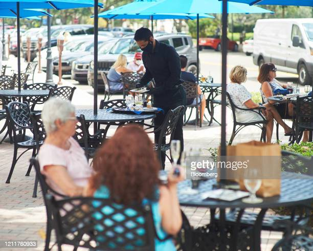 A server wearing a protective mask and gloves cleans a table in the outside dining section of a restaurant in St Petersburg Florida US on Monday May...