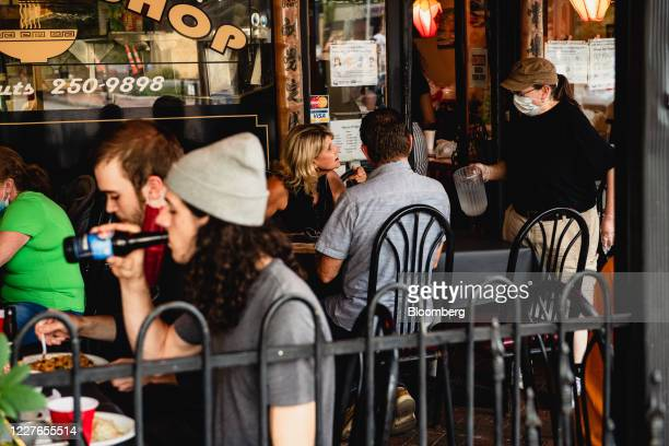 Server wearing a protective mask and gloves speaks with customers at the outside seating area of a restaurant in downtown Asheville, North Carolina,...