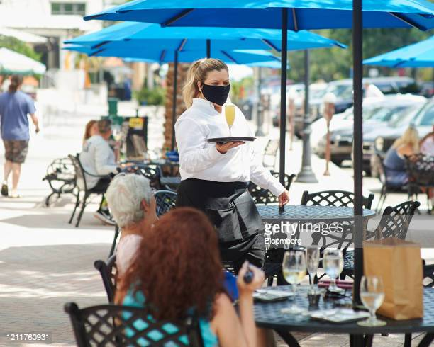 Server wearing a protective mask serves a drink to a customer in the outside dining area of a restaurant in St. Petersburg, Florida, U.S., on Monday,...