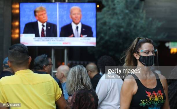 Server wears a face shield and face covering as people sit and watch a broadcast of the first debate between President Donald Trump and Democratic...
