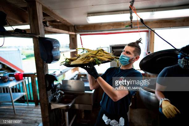 Server wears a mask and gloves while working, as Hoopers Crab House opens for in-person dining, amid the coronavirus pandemic, on May 30, 2020 in...