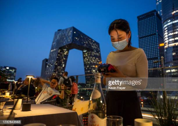 Server wears a protective mask as she processes a payment at a restaurant overlooking the Central Business District on May 12, 2021 in Beijing,...