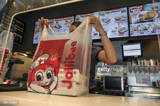 Service assistant prepares a customer's take-out order at the Jollibee Foods Corp. Restaurant in Taguig City, Manila, the Philippines, on Saturday,...