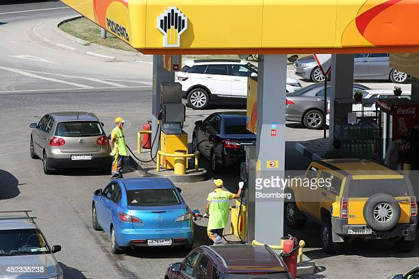 Service attendants use fuel pumps to fill automobiles on the forecourt of an OAO Rosneft gas station in Moscow Russia on Friday July 18 2014 Russia's...