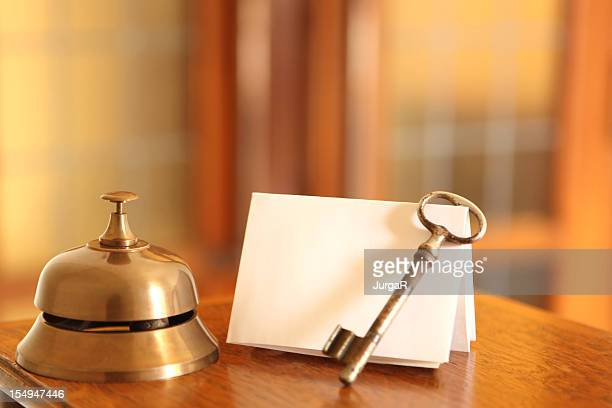 service bell, old fashioned door key and card in hotel lobby - hotel key stock photos and pictures
