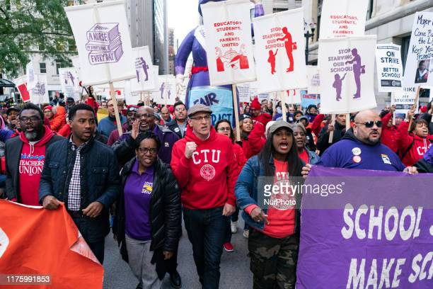 Service Employees International Union President Dian Palmer marches with Chicago Teachers Union President Jesse Sharkey and Vice President Stacy...