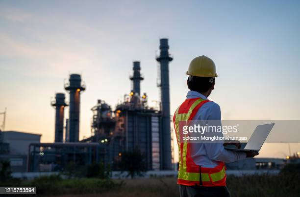 service engineer is working at electric power plant with laptop - atomic imagery stock pictures, royalty-free photos & images