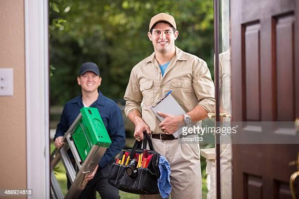 Service Branche: Zwei multi-ethnischen repairmen an Kunden vor der Tür.