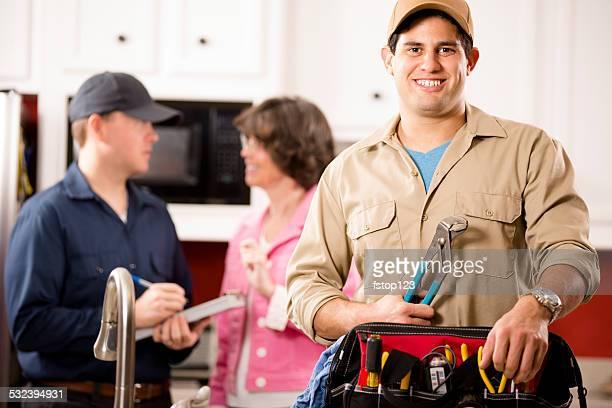 Service secteur: Deux multi-ethnique repairmen travail au client de chez vous.