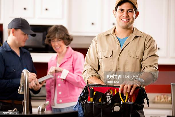 Service Industry: Two multi-ethnic repairmen work at customer's home.
