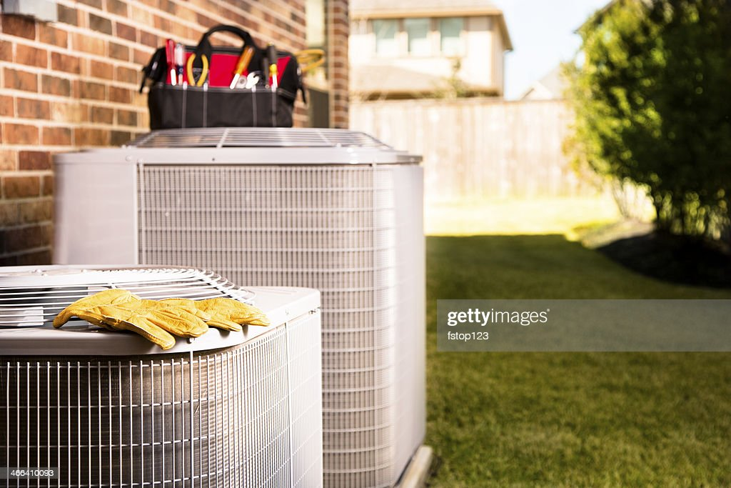 Service Industry:  Work tools on air conditioners. Outside residential home. : Stock Photo