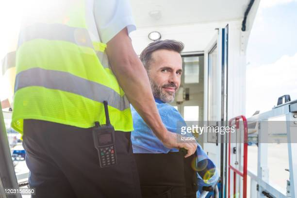 service man helping disabled passenger to enter on board at airport - persons with disabilities stock pictures, royalty-free photos & images