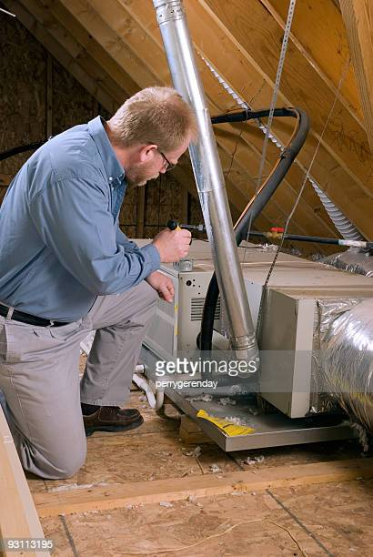 Service Man Inspects Furnace