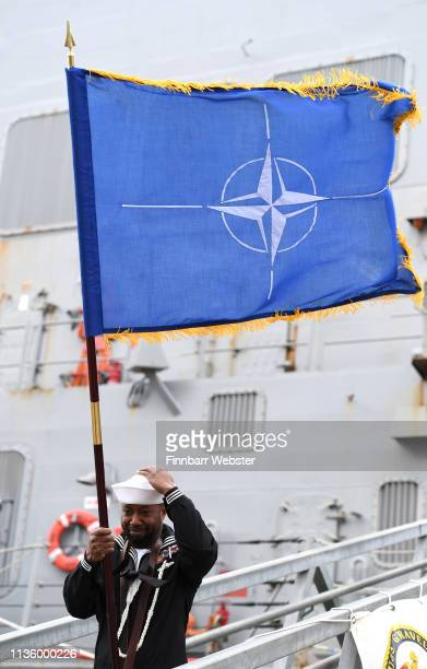 A service man poses for the media with a NATO flag at the Devonport Naval Base on March 15 2019 in Plymouth England Two NATO Maritime Groups have...