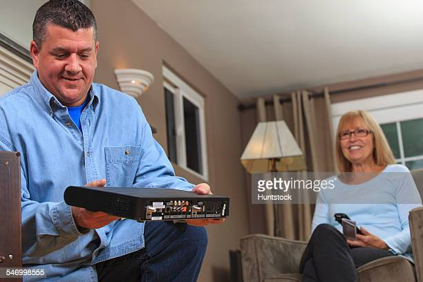 Service man preparing to install a cable box for homeowner