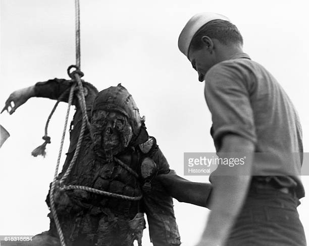 Service man uses a rope and winch to bring the body of a soldier killed in the attack on Pearl Harbor aboard a ship, circa 1942.