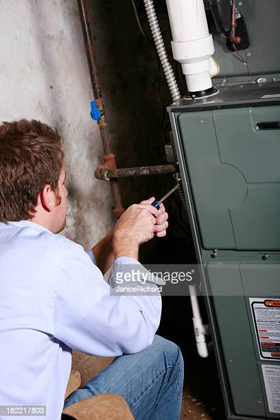 A service man working on a home furnace