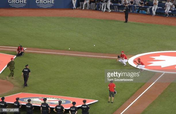 A service member of the Canadian Armed Forces and a Toronto Police officer throw out the first pitch simultaneously to John Axford of the Toronto...