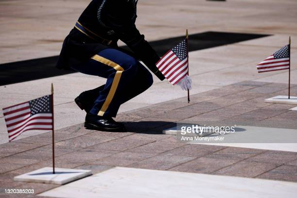 """Service member places a flag at the Tomb of the Unknown Soldier as part of the """"Flags In"""" ceremony ahead of the Memorial Day weekend at Arlington..."""
