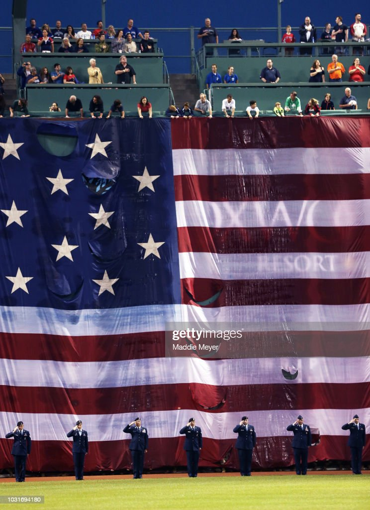 Service members stand in front of an American flag draped over the Green Monster to commemorate September 11 before the game between the Boston Red Sox and the Toronto Blue Jays at Fenway Park on September 11, 2018 in Boston, Massachusetts.