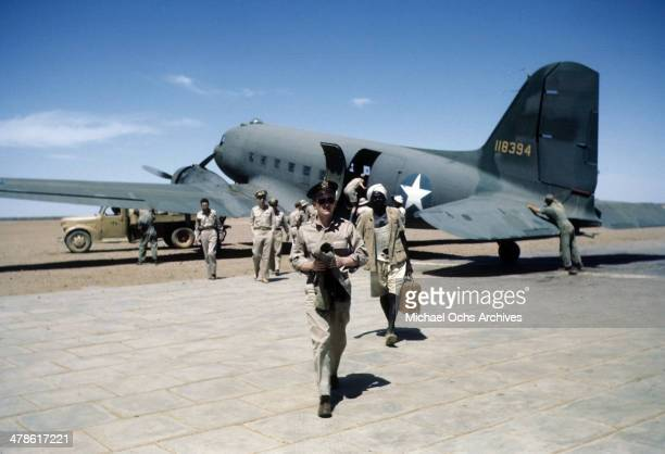 US service men exit a C47 Skytrain plane on the Wadi Seidna runway at the US Army Air Force/Royal Air Force base in Khartoum AngloEgyptian Sudan