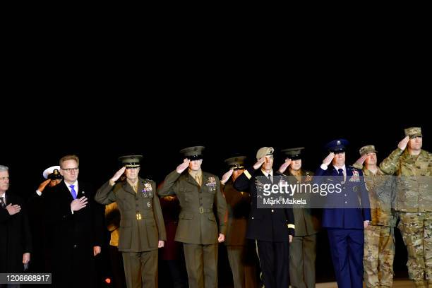 Service men salute during a dignified transfer for fallen service member US Marine Gunnery Sgt Diego D Pongo at Dover Air Force Base on March 11 2020...