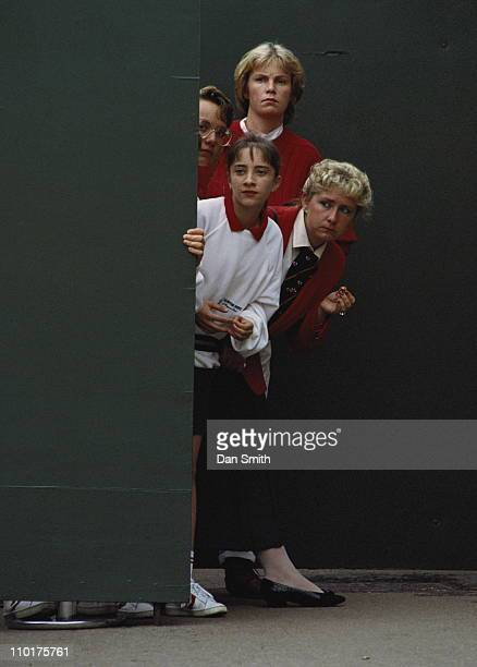 Service staff peak around a door to look at the action at the Stella Artois Lawn Tennis Championship on 6th June 1988 at the Queen's Club in London...